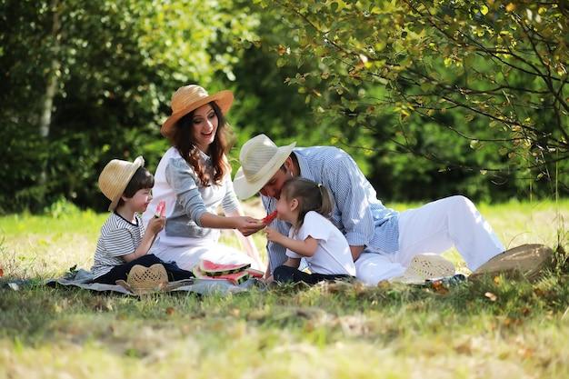 Famiglia felice con bambini che fanno picnic nel parco, genitori con bambini seduti sull'erba del giardino e che mangiano anguria all'aperto