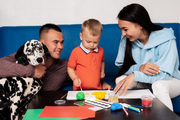 Una famiglia felice con un cane dalmata è impegnata in un lavoro creativo a casa e si diverte