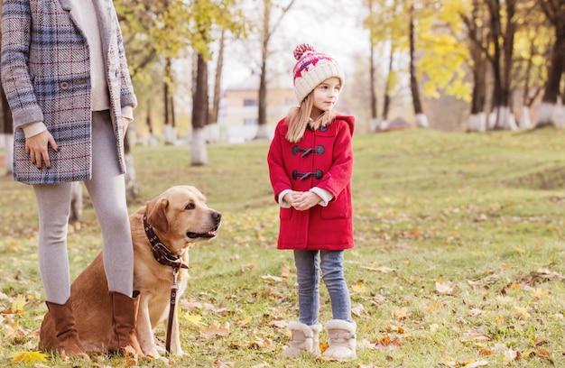 Famiglia felice con il cane nella soleggiata sosta di autunno