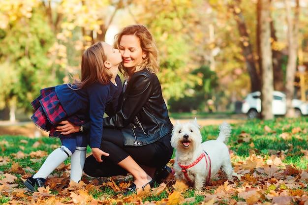Famiglia felice con il cane sulla passeggiata nel parco cittadino di autunno. figlia del bambino e della madre che gioca con le foglie di autunno.