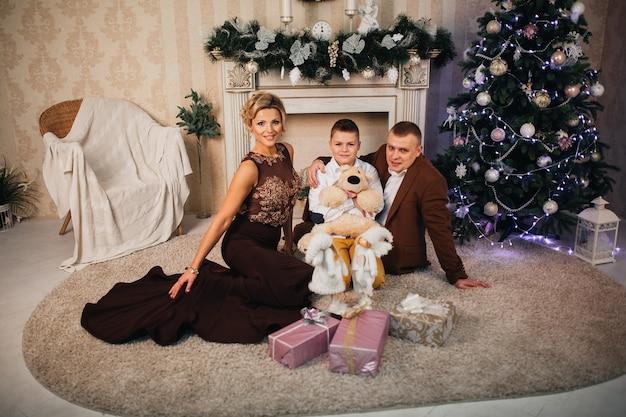 Famiglia felice con doni intorno all'albero di natale e al camino