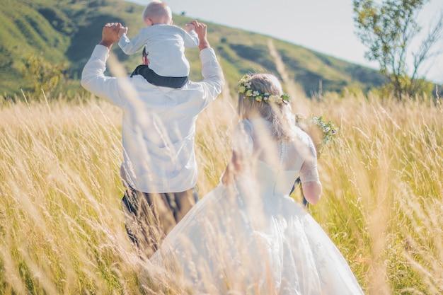 Famiglia felice con bambino che cammina insieme nel campo di grano in una calda e soleggiata giornata estiva. focalizzazione morbida.