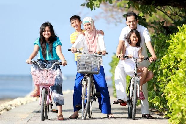 Famiglia felice con bambini in sella a biciclette