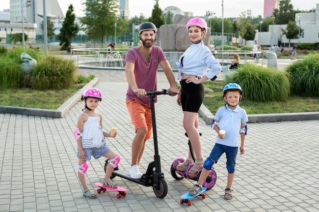 Famiglia felice con bambini che guidano su segway, scooter elettrico e skateboard nel parco in estate, bambini che mangiano il gelato.
