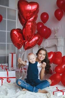Famiglia felice con i piccoli neonati in atmosfera festiva su sfondo di palloncini e scatole regalo