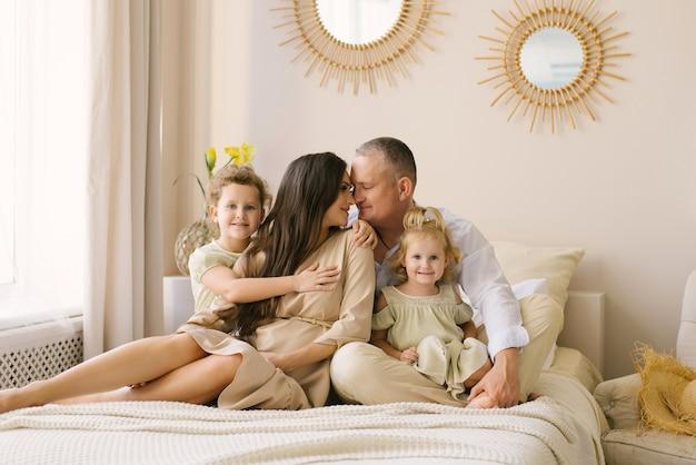 Famiglia felice con figlie sedute sul letto, mamma e papà si toccano e sorridono, i bambini abbracciano i genitori. buon fine settimana mattina