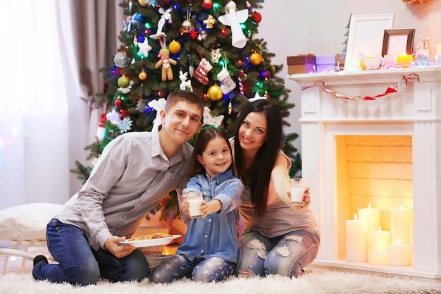Famiglia felice con latte e biscotti dolci nella stanza di natale decorata