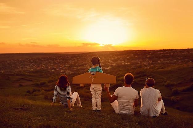 Famiglia felice con la natura la sera al tramonto