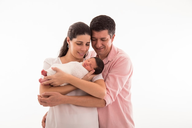 Famiglia felice con neonato su sfondo bianco.