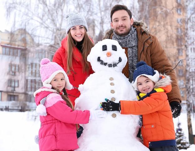 Famiglia felice con pupazzo di neve nel parco in vacanza invernale