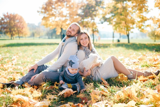 Famiglia felice con il loro ritratto all'aperto del bambino nel parco di autunno