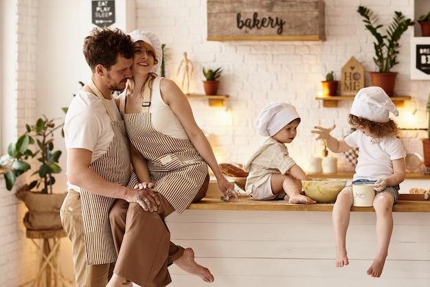 Famiglia felice con i loro figli che cucinano in cucina