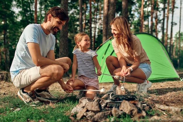 Una famiglia felice con la figlia è seduta accanto al fuoco vicino alla tenda e durante il fine settimana frigge marshmallow in una foresta di pini. campeggio, ricreazione, escursionismo.