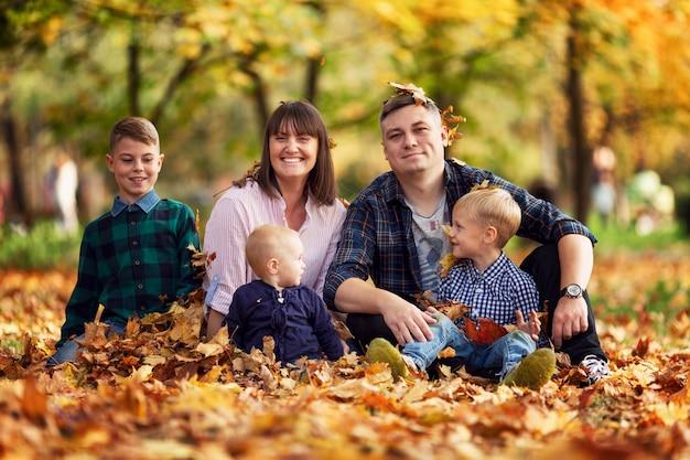 Famiglia felice con tre bambini sono seduti nel parco in autunno tra il fogliame giallo caduto