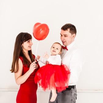 La famiglia felice con il bambino selebra il giorno di san valentino