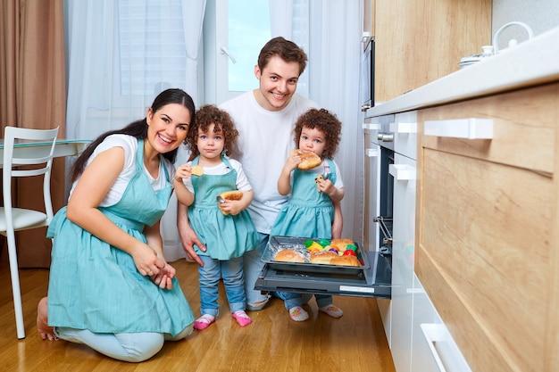 Famiglia felice con figlie gemelle in cucina madre allegra padre due figlie gemelle che preparano cibo in cucina il concetto di una famiglia felice happy