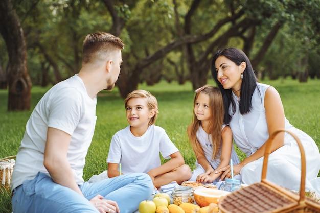 Famiglia felice con due bambini che si rilassano sul prato durante un picnic nel verde del giardino.