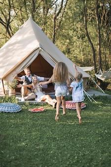 Famiglia felice con due bambine all'aperto vicino ai tipi di wigwam tenda in stile rustico boho