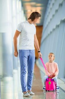 La famiglia felice con due bambini in aeroporto si diverte ad aspettare l'imbarco