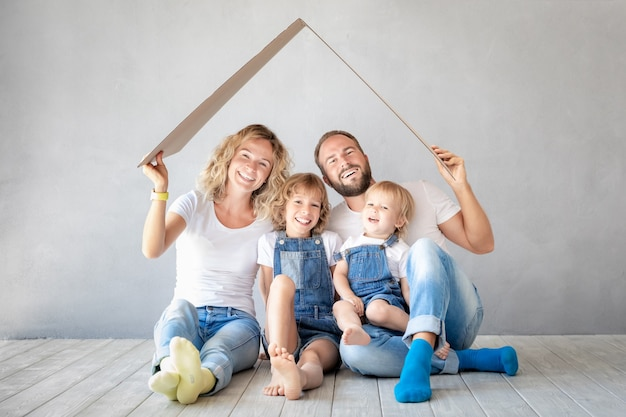 Famiglia felice con due bambini che giocano nella nuova casa