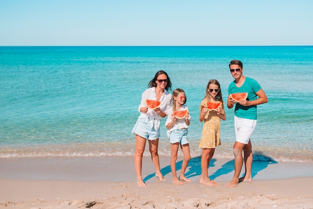 Famiglia felice con anguria sulla spiaggia. genitori e bambini in riva al mare che si divertono.
