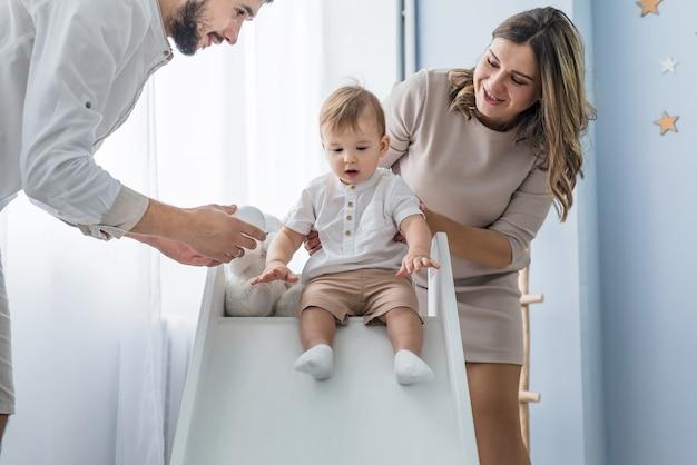 La famiglia felice con un giovane figlio gioca insieme sullo scivolo dei bambini di casa