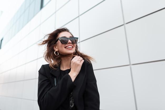 Ragazza felice di modo in vestiti neri alla moda
