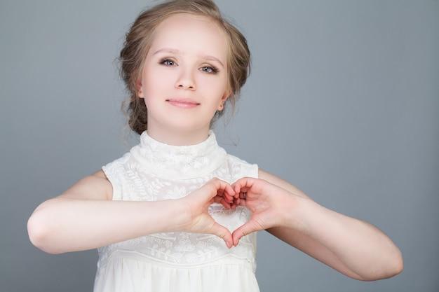 Ragazza felice del modello di moda che fa cuore. concetto di amore