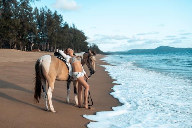 Giovane donna alla moda felice che posa con un cavallo sulla spiaggia