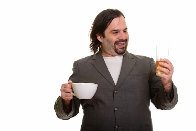 Uomo d'affari caucasico grasso felice che sorride e che sceglie la birra sopra il caffè