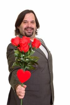 Felice uomo d'affari caucasico grasso sorridente dando rose rosse e cuore pronto per il giorno di san valentino