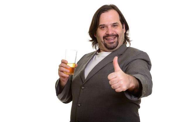 Uomo d'affari caucasico grasso felice che sorride e che tiene vetro dell'orso mentre dà pollice in su