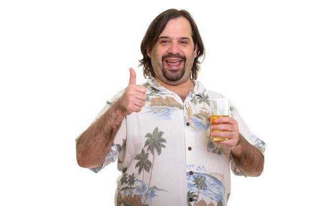 Uomo caucasico grasso felice che sorride mentre dà pollice in su e che tiene un bicchiere di birra pronto per le vacanze
