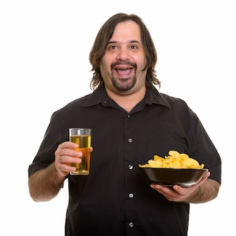 Uomo caucasico grasso felice che sorride mentre tiene ciotola di patatine fritte e bicchiere di birra