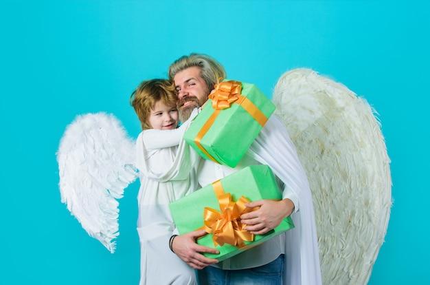 Felice padre in costume da angelo con figlio piccolo angelo tiene in mano un simpatico angelo di san valentino padre