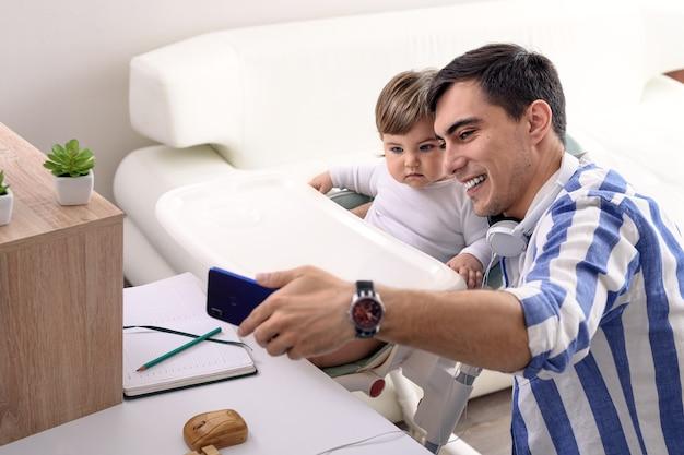 Il padre felice in camicia blu prende selfie sullo smartphone con il bambino in appartamento, concetto di paternità felice