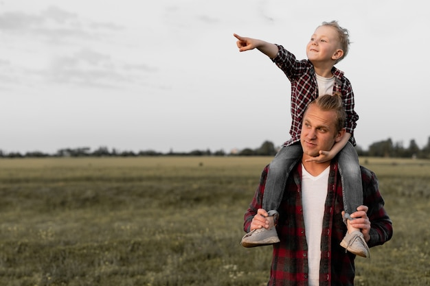 Un padre felice porta un figlio sulle spalle.
