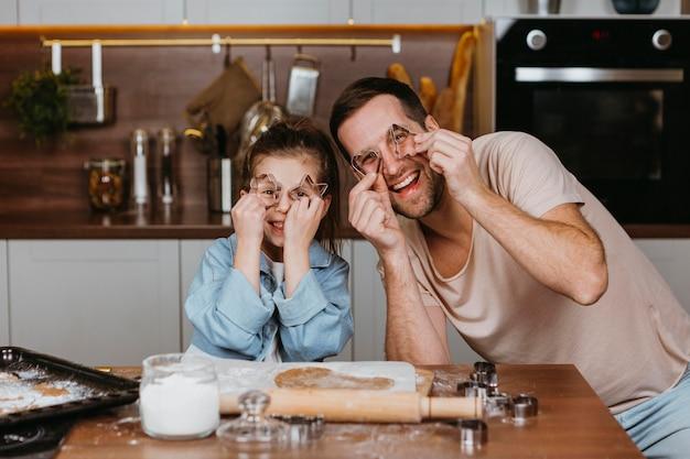Padre felice e figlia che cucinano insieme a casa