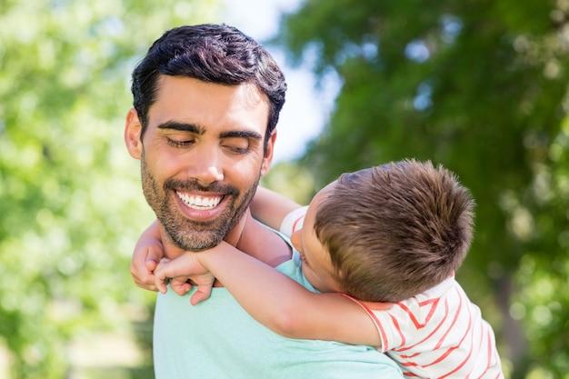 Padre felice che dà sulle spalle giro a suo figlio