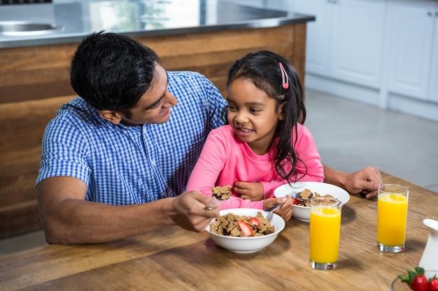 Padre felice facendo colazione con sua figlia