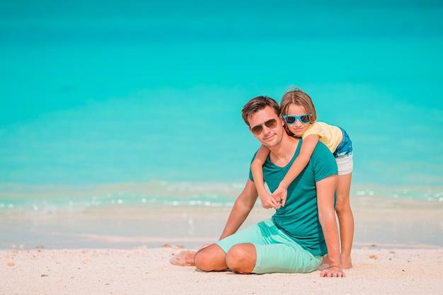 Padre felice e la sua piccola figlia adorabile alla spiaggia di sabbia bianca divertendosi