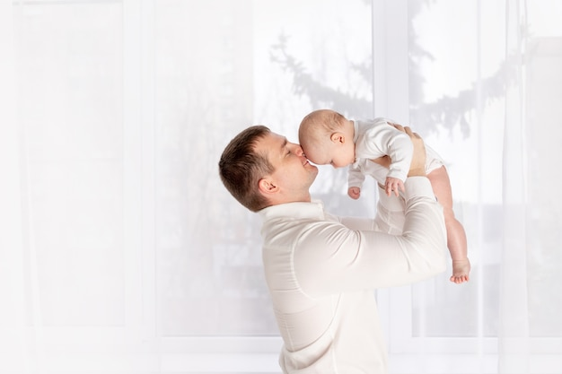 Il padre felice bacia il neonato a casa vicino alla finestra, il concetto di famiglia amorevole felice, la festa del papà