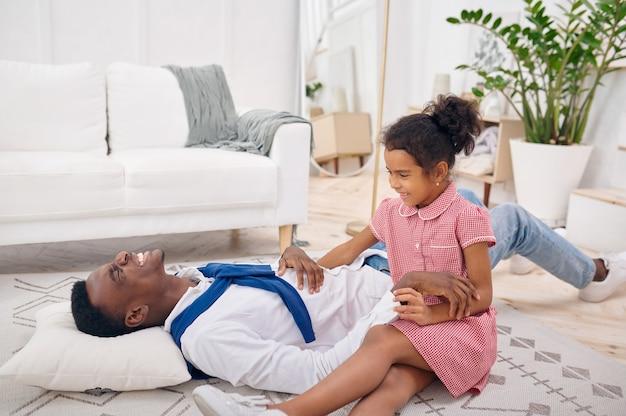 Padre felice e figlia piccola giocano in soggiorno in