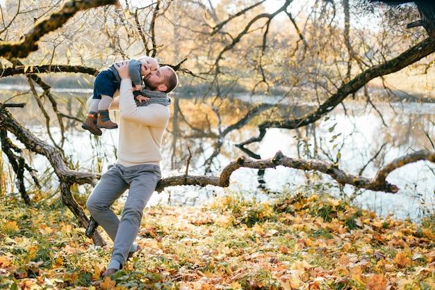 Padre felice che gioca con il suo piccolo bambino nel parco di autunno