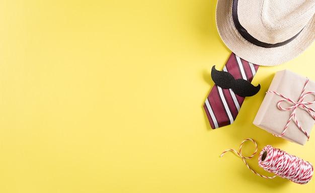 Concetto di sfondo per la festa del papà felice con cravatta e baffi, cappello, confezione regalo su sfondo giallo pastello.