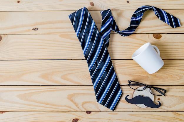 Concetto di festa del papà felice. una carta per baffi neri, una cravatta blu, una confezione regalo blu e bicchieri su un tavolo di legno.