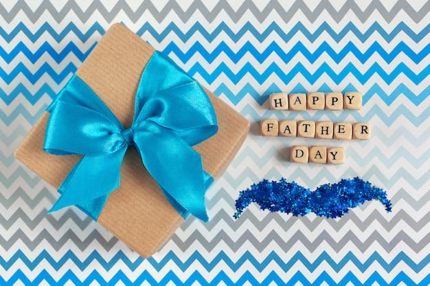 Cartolina d'auguri felice di festa del papà con il contenitore di regalo decorato sul fondo a strisce di zigzag.