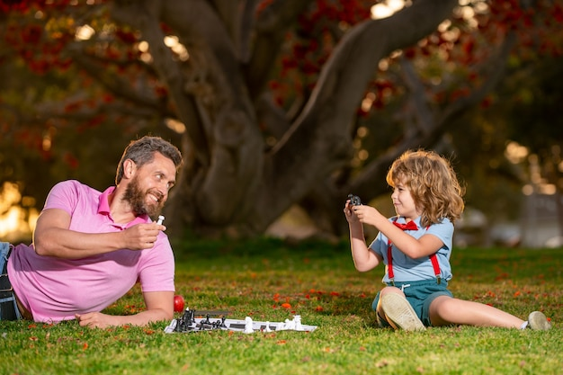 Felice padre e figlio che giocano a scacchi sdraiati sull'erba al parco del prato festa del papà e concetto di genitorialità