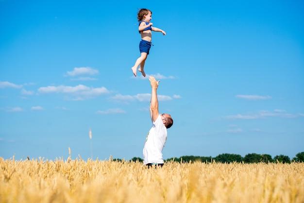 Padre felice in piedi in mezzo al campo lanciando suo figlio che indossa cappelli pantaloncini e magliette il giorno d'estate su sfondo blu cielo