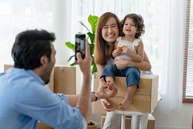 Padre felice che cattura foto di sua moglie e figlia piccola da smartphone nella nuova casa
